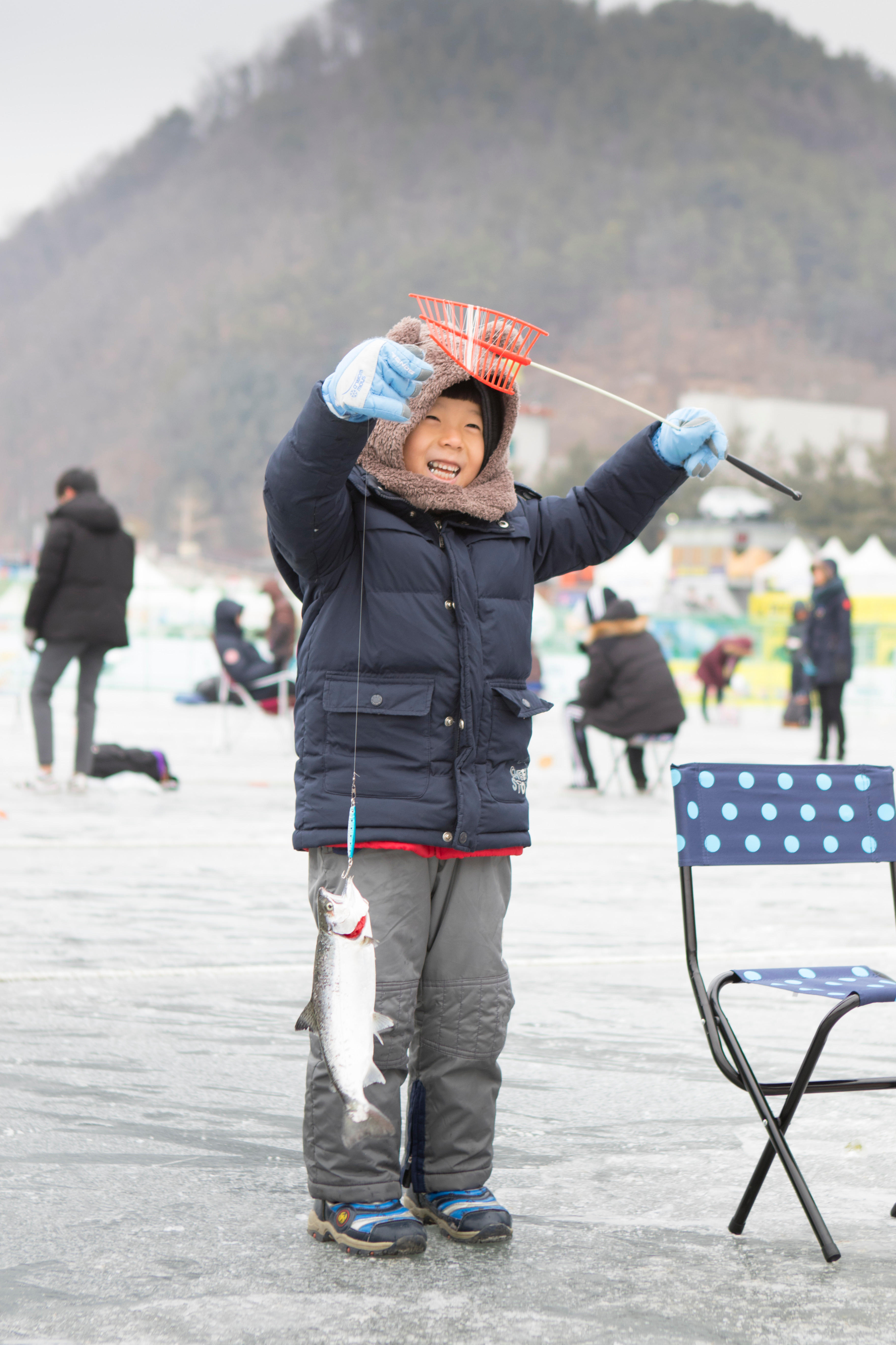 A young boy is happy with the fish he caught during the ice fishing festival at Hwacheon Sancheoneo in the Gangwon-do region of South Korea.  The Hwacheon Sancheoneo Ice Festival is a tradition for Korean people. Every year in January crowds gather at the